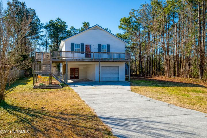Affordable home in desirable Sneads Ferry with NO HOA and NO city taxes, and  close to everything!!  MarSOC, Air Station, Courthouse Bay, and  back gate to Camp Lejeune, the beach and the water!  Boat ramp is close by!!!  This home lives large even with the 2 bedrooms 1 bath.  It has an inviting open floor plan with a corner fireplace for those chilly Carolina nights!  The double car garage downstairs offers plenty of room for a workshop for the handyman in the family Plus there's still room for  a home gym or work out center!  (Or of course you can always use the garage for your cars, trucks and boat!) Metal roof 2018; new  deck on the front and sides of the house; master bath has tile walls and floors, double sink vanity; new hot water heater!   The kitchen is designed for the cook in the family with lots of cupboard space!! Home is in a AE flood zone, on country water and Pluris sewer!  Come check it out quickly before it is gone!