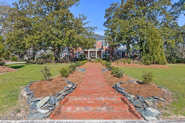 Woodland Manor is more than a house, it's an estate that remains timeless through all generations just as it was intended by the original building family, W.T. Turlington, MD. It is bookended by two very similar estates which gives this property a complete story. Woodland Manor is nestled quietly in downtown Jacksonville but has the serenity of a quiet countryside with picturesque views of Chaney Creek. Woodland Manor's landscape was designed for beauty, pleasure for every season and remains very close to its original design. The exterior and interior design is Georgian; however, is very flexible and one that many family arrangements can enjoy. The main floor consists of the East & West wing-each with a primary suite and woodworking fireplace. The main floor also consists of a family size eat-in kitchen, beverage/wine room, dining room, music room with fireplace, gentleman's study, 3 bathrooms and a large laundry workroom. The second level of the manor consists of 4 large bedrooms, two full-size bathrooms and attic access to plentiful storage. The stairwell and landings between the two main floors will take your breath away! In search of someone to love this house, not just buy it.