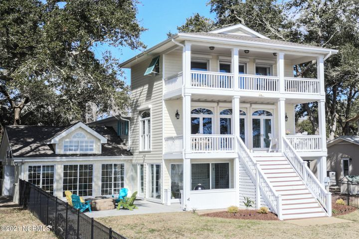 Sunrise views filtered through mature oaks is the iconic Coastal NC scene.  This luxurious coastal cottage is also a boater's paradise that comes with two lifts, a covered dock, and a private launch that are only a short walk from your living room.  Perfect for families and entertaining with an adorable fenced-in backyard, cozy firepit, and spacious heated sunroom. This beauty will have you seeing double as it includes two boat lifts, two docks, two living rooms, and two master suites. Enjoy morning coffee from your private master suite balcony and panoramic views of the Intracoastal Waterway, Topsail Island, and Serenity Point.  Luxurious upgrades include Wolf appliances, a subzero refrigerator with cabinet-matched panels, hardwood flooring through the top two floors, and tile throughout the finished basement as well as Bahama and rolling hurricane shutters. This breathtaking view also comes with a home office, full two-car garage, circle driveway, and is only minutes from Olde Point Country Club and NC's award-winning beaches.  Call today to schedule your private tour and see the features sheet for more details!