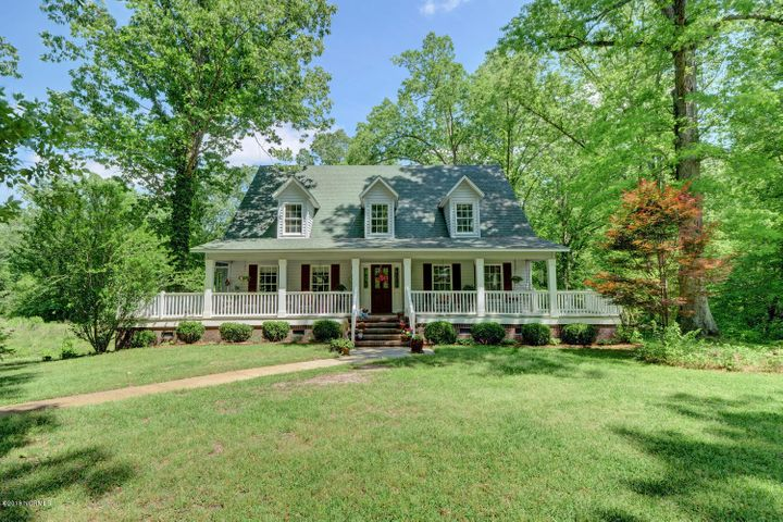 Looking for that needle in a haystack?  I found it!!  Tucked away on over 5 acres that seems to be an escape from the world, but is located a few minutes from all major highways, schools, shopping and bases is this exceptional , one of a kind home.  Breathe out as you come down the long tree lined winding driveway to this Southern style home with so much to offer.   The inviting oversized wrap around porch is a start.   This home has a large foyer, upgraded kitchen with granite counter tops, upgraded cabinets, tons of storage and working space,  a formal dining room with tons of windows for extra light and is placed perfectly to enjoy the spring fed pond.  The family room is oversized as well for many furniture placement options.  This beauty has a HARD TO FIND downstairs master bedroom, walk in closet and a large master bath.  Upstairs you will find 3 large bedrooms.  This home was built with lots of storage in every room!!  It does not stop here.  The basement has been finished, perfect for more family space, a playroom, or home office, and additional unfinished spaces for more storage.    Need more space?  The home comes with a detached 2 car garage, a heat single bay workshop, and a completely finished efficiency apartment above the garage.    This is truly a one of a kind!