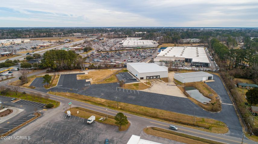 Two metal top of the line warehouse buildings totaling 26,289 square feet centrally located in New Bern, NC. Main warehouse building has 19,049 sq ft with 3,200 sq ft of it consisting of 6 offices, 1 conference room & 1 large meeting room with all new carpet & LVT flooring. Remaining 15,849 +/- sq ft is warehouse space with 4 loading docks & overhead door access to building & 25 ft plus ceilings. Second warehouse offers 7,500 sq feet & includes open high ceiling warehouse space, bathroom, parts & mechanics tool room & drive through covered truck wash down/repair area. Entire property is fenced with keypad entry & 50+ parking spaces. Property is zoned I-1 and not located in a flood zone. Property has 575 ft on Red Robin Ln & 437 ft bordering Southgate. Property is next to Lowe's Home Improvement & located right off of Dr. MLK Blvd. Utility provider is City of New Bern.  Property outside of fence bordering Garden Center Lane not included in this sale and will be assigned a PIN once subdivided