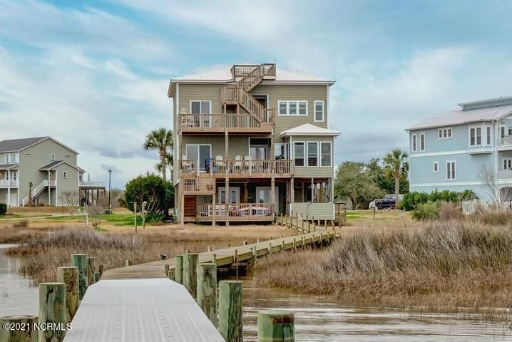 Waterfront living at its very finest. Located in the premier community of Pelican Point, this gorgeous coastal home offers breathtaking water views. As you enter the foyer of this unique residence, you can take the elevator or ascend the stairs to the open atrium living area.  Surrounded by the balcony on the second story, you will notice the natural light that brightens the space. One of the highlights of the home is the gorgeous gourmet kitchen. Complete with a Verona gas stove, granite countertops, custom soft close cabinetry, and a large butler's pantry, this kitchen is designed and equipped to satisfy the needs of the true Chef in the family. Along with a wet bar and coffee bar, this home is designed for entertaining. The home has 3 bedrooms, 3.5 baths and a large, finished basement. The home sits on the Intracoastal Waterway and offers a pier and covered boat dock.  Need some time alone, climb the stairs to the widow's walk and feel the breeze coming off the Atlantic. If you are looking for a one-of-a-kind home on the water, look no further - you are home.