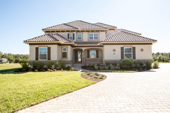 This Mediterrenean style home is situated on a cul-de-sac and features a tile roof and large pavered driveway.