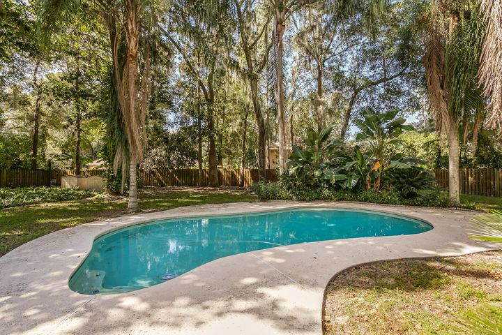 Large in ground swimming pool with fenced backyard and natural landscaping
