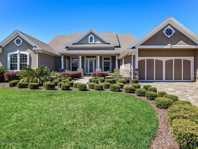 Beautifully landscaped home with brick paver driveway