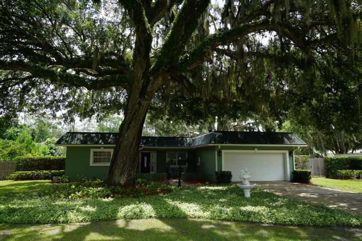 A majestic live oak shades the front of this lovely home