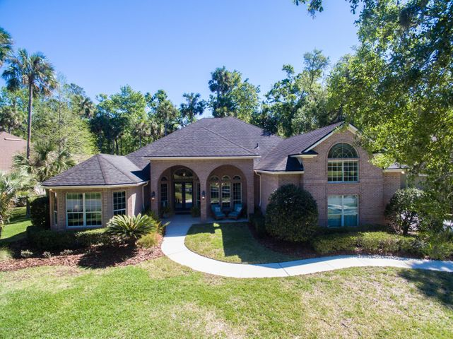 This gorgeous brick home is situated amongst mature trees and features water and treed views across the street