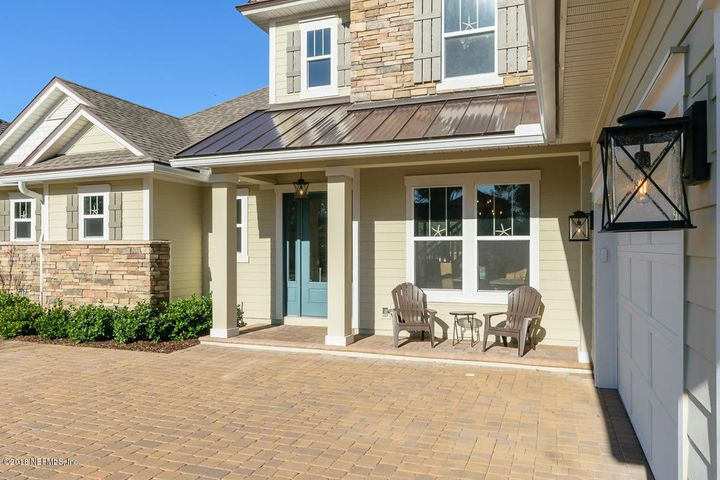 Rocking chairs accent this charming front porch with stone accents and metal roof.