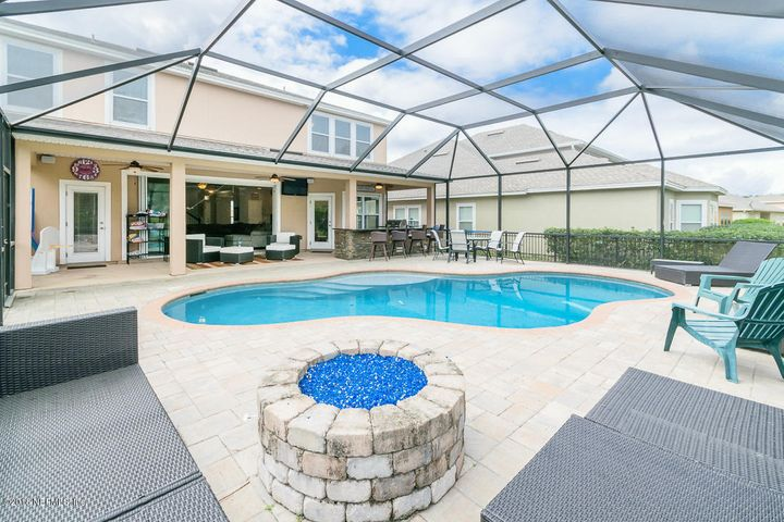 Spacious backyard oasis! Featuring large lanai with screened in pool and fire feature