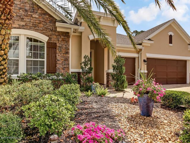 The front yard features lovely tropical landscaping.