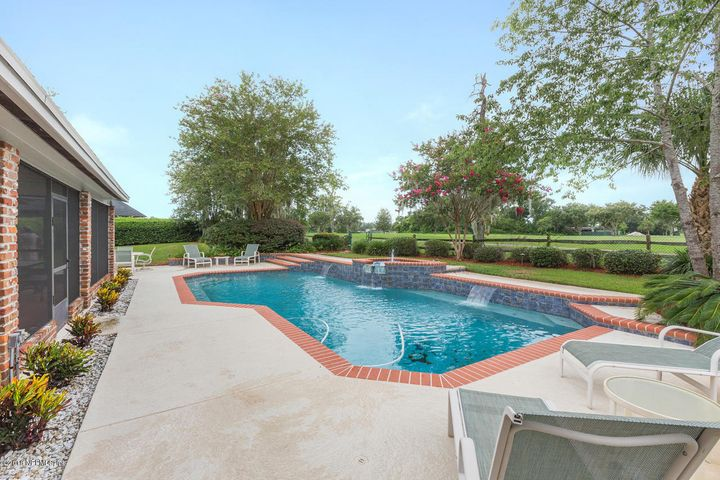 Three separate fountains in the pool with golf course views.
