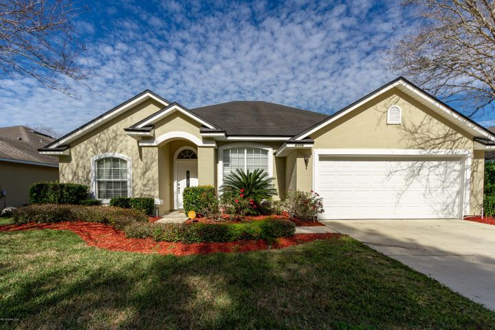 Curb Appeal includes a sidewalk and very large Crepe Myrtles in this Gated Golf Course Community