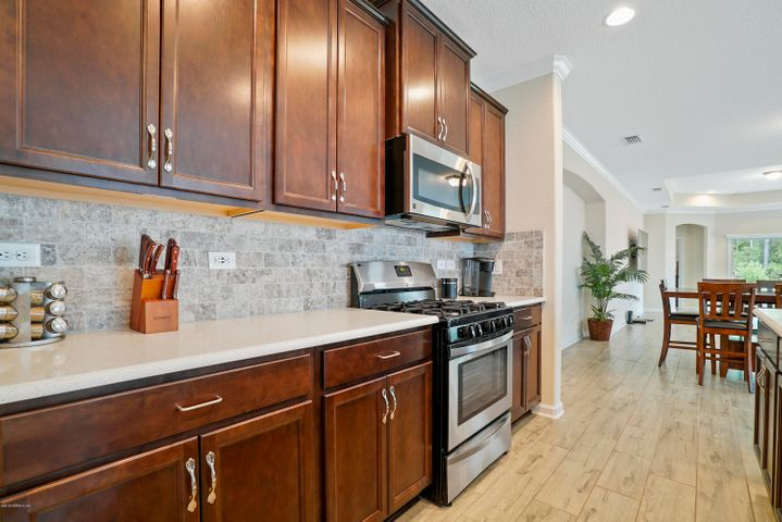Luxury upgrades in the kitchen include vented microwave, Stone tile backsplash and granite countertops