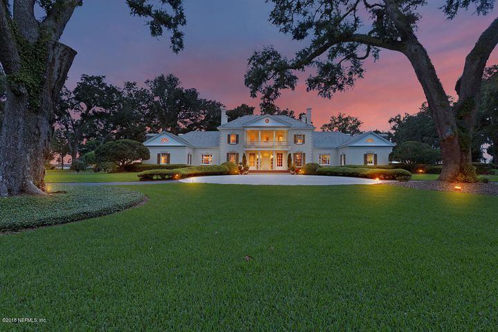Southern Classicism along 14.5 acres of St. Johns riverfront. Spectacular opportunity to amass 600 ft of HIGH BLUFF river frontage and a splendid estate home offering the look of a Georgia Plantation. The river elevation provides more open fenestration to capitalize on the views of lawn, live oaks and of course the tidal waters of The St. Johns River.  The south wing of home contains a suite of three bedrooms and three baths offering comfort and privacy. The north wing contains the kitchen, morning room, office, mud room & secured storage space,  The master suite located on second floor occupies fully half of the central portion of the home opening onto a balcony overlooking the river. An outbuilding on the property includes a two bedroom apartment and a caretakers office and addl garage. The outdoor amenities add to the ambience of this retreat including pool, ponds and an 1100 foot NEWLY built pier that offers deepwater dockage on the river.   Remarkable list of details are separately listed and can be found under document section of MLS.