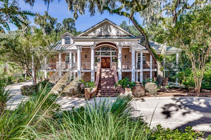 Custom built, one of a kind three story family home located in the heart of Ortega on the river close to downtown. Solid copper roof and filled block, steel and brick construction and exquisite weeping mortar joints make this home a fortress. Wrap around porches on the first and second floor offer magnificent views. Located high on a bluff with majestic oaks, this home is spectacular inside and out. The grand foyer houses a handcrafted double freestanding mahogany stairway. Custom moldings throughout. The four queen bunk/recreation room is the gathering spot for kids of all ages. The Mother-In-Law/Nanny suite downstairs is a definite plus. Fixed generator will service the entire property including pool house and dock. Dock can accommodate 70 foot vessel. So much charm & thoughtful details.