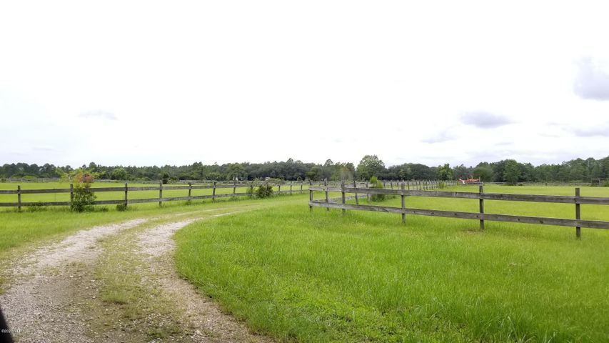 Looking for a large family compound or horse boarding facility in St. Johns County? You found it in this sprawling, gated Ranch that spans 30.83 acres!!! PRIME LOCATION w/fencing,  cross fenced grazing pastures, quarantine stalls, large round pen, irrigation in all paddocks, feeding stalls, run in sheds & wash racks. Two spring fed ponds stocked w/bass, bream & catfish. Several power poles on property. Property is high & dry, Flood zone X. Currently zoned Open Rural/Agricultural and for future Silviculture use. There are 3 mobile homes on the property that have no value. Guana Preserve riding trails are nearby. Just minutes away from the Ponte Vedra beaches, Nocatee, schools & shopping! Note: If you run a business and live here, you can have your taxes exempted agriculturally!