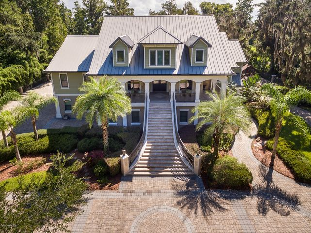 This is no ordinary home! In fact, it would be difficult to find a more magnificent country riverfront estate! Located just 7 miles south of the new outer beltway (which is now under construction) this property is not far from town.  It IS, however, far from ordinary! This one owner home has way too many features to list here but the owners have not missed a thing! The home has over 10,000 sq. ft. under roof with 6400+ sq ft. being heated and cooled. The estate includes a resort style pool with a bridge, a summer kitchen and T.V. area, covered boat slip and lift, a RV port w/50 amp service,4 car garages, a play ground, a storage shed, paver drive, generator and gates.The home is custom in every aspect with fine finishes and materials throughout its immaculate interior.  (see feature sheet) Inside the home boasts a 28 ft. high, living room, a gourmet kitchen w/butlers pantry, an elevator, a huge master suite with morning kitchen, truly impressive master bath with steam room, flow over tub, onyx counters and more, on the ground floor is a complete in-law/guest apartment with its own entrance, there are bedrooms on 3 levels, a smart home system, an office w/coffered wood ceiling and matching cabinetry, an exercise room, a recreation room, a huge laundry room, and more! The views of the three mile wide St. Johns river are simply amazing! All buyers must be pre qualified for showings but this home is well worth a little extra effort to see! This home is full of surprises!