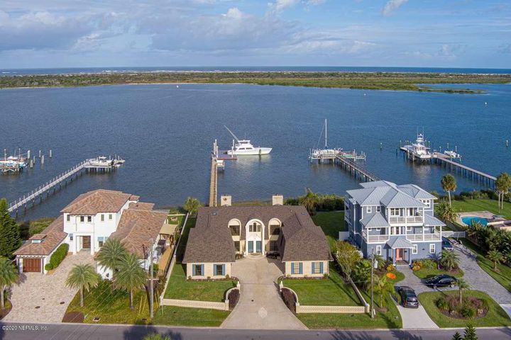 One of the most recognized and iconic waterfront homes in Davis Shores and just a stone's through away from the St. Augustine Inlet and Atlantic Ocean, this elegant home was custom built by the Collier's Family who developed signature waterfront properties along Salt Run in St. Augustine. Designed with luxury in mind for the waterfront enthusiast, this home can accommodate a myriad of uses and is currently designed as two separate 3,000 SF +/- residences, each with their own 2 car garage, fireplaces, a single inground pool, and walled courtyard. The dock can accommodate a 65-foot or larger sportfish with ease which is a rarity to find among waterfront properties in St. Augustine as well as numerous configurations for multiple vessels based on it being a modular, floating dock system. The southern residence has been professionally decorated and contains a formal dining room, a living room with a fireplace, an eat-in kitchen and a family room area overlooking the pool, and full bath on the first floor. The second floor includes a master bedroom suite overlooking the water, a den/office or 3rd bedroom, a rear guest bedroom suite with its own separate outside entrance, and a laundry room. The northern residence has recently been white boxed and is a clean slate ready for a new owner's designer touches. The first floor is an open concept with a sunken living or dining room area, which was created for intimacy in large open spaces, a contemporary winding staircase with a clear story to the 2nd floor, also an elevator; a galley style kitchen, a full bath and laundry room. The second floor has a grand open master bedroom suite which could also accommodate a 2nd floor family room, and a rear guest suite with a spiral staircase which provides separate access to the first floor. Whether you wish to have one 6,000 SF +/- residence or have ideas of a master waterfront compound that accommodates two different families or a separate vacation rental, the options are yours!