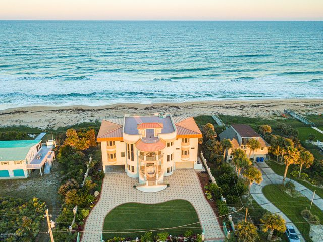 You're invited to a truly unique oceanfront estate located in South Ponte Vedra Beach. Tucked into the high dunes on a deep lot, this 6BR/5.5BA home's splendid marriage of distinctive architecture, high-quality construction, exemplary stone & millwork, and panoramic views of the Atlantic Ocean & Guana Preserve will inspire you. Features circular driveway with 2 entry gates., expansive custom linen & clothing closets, chefs kitchen & pantry, wet bar, great room, 3 living areas, office, master suite, 2 laundry zones,4-car parking (covered & garage) & vast motor court, rooftop terrace & expansive balconies & patio. Rising four stories above the surf & sand, this beach home fortress features both private & public living spaces, perfect for those with an appreciation for nature and creativity. The most coveted area of South Ponte Vedra Beach, situated on a deep lot with high dunes. Built like a fortress, all concrete construction with rebar & filled cells sitting atop 30 pilings sunk 25' deep. Owners focused on the highest quality of construction and features that include: storm impact door & windows, marble & wood floors, 5 zone AC, central vac, large covered terrace  to enjoy the ocean breeze that leads to a private walk-over to to the ocean. Take the spiral staircase or elevator to the 4th floor, 1500sf, roof top deck capturing the most spectacular views of the Atlantic Ocean & Guana Lake.