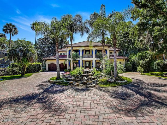 WATERFRONT property 100 ft on Intracoastal Waterway navigable to the ocean sits on .92 acres on sought after Roscoe Blvd. Outdoor lover's paradise perfect for entertaining w/ 2 boat lifts, floating dock and heated screened in pool w/ spa. Custom and top of the line builder's estate on a premier lot is nestled among giant old oak trees w/ the best amenities. Luxurious features include: hand-crafted custom cabinetry t/out, 3 fireplaces, 2 laundry rooms, coffered ceilings in the living rm. plus, wet bar w/ dishwasher, ice-maker & built-in coffee maker.  Kitchen is a chef's dream w/ 2 built-in refrigerators, 2 ovens, induction cook top, cozy fireplace, working areas & a full size wine cooler. Separate 1 bedrm guest house & 4.5 car garage w/ wrkshp. Main house 5,680 sq ft Guest house 528 sq ft