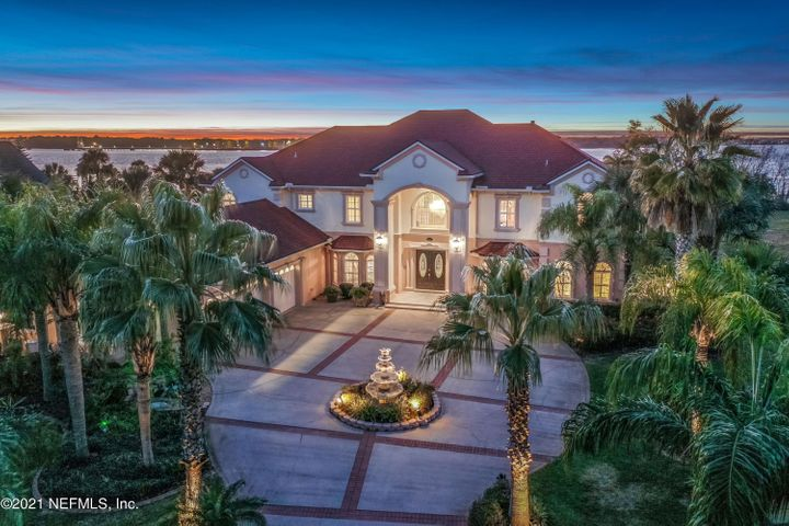 As you drive down the palm-tree lined entrance to Rive St. Johns you will know you have found a hidden gem in this picturesque riverfront community. Elegant & inviting this custom-built insulated concrete form (ICF)  constructed riverfront home is built to perfection. Boasting over 5,800 sq ft this 5-bedroom, 6 bathroom home is the epitome of Florida outdoor living overlooking the wide views of the St Johns River. From the moment you enter the home you are greeted by the two-story foyer w/sweeping staircase, meticulously hand-painted by local artists, opening to the exquisite living room, w/cast-stone fireplace, & dining room, w/authentic Swarovski Spectra Crystal chandelier, all w/ spectacular water views. Gourmet kitchen, adjacent to the family room, boasts 5-burner gas cooktop, stainless steel appliances, Blue Volga granite counters, Tyent water ionization system, walk-in pantry, & is perfect for family gatherings or entertaining w/easy access to the pool & outdoor living area. This home boasts 2 master suites, w/river views, walk-in closets & spa baths. The upstairs master suite w/cast-stone fireplace, & river views from the balcony, will be the favorite or maybe you would rather be downstairs w/your quaint private terrace & river views, perfect for enjoying your morning coffee in privacy. The downstairs suite is perfect as a guest-suite or in-law suite. Two separate offices, one upstairs, located off the master bedroom boasts a closet making it perfect as a study or nursery, & one downstairs, all you need for those working from home. Upstairs boasts Brazilian Cherry hardwood floors, 3 ensuite bedrooms & expansive family room w/cast-stone fireplace & wet bar, the perfect game room. Step outside to the 2nd-story expansive balcony w/cedar tongue & groove ceiling & enjoy the stunning views. Enjoy dining al fresco & entertaining friends & family no matter how big or small the gathering...for small intimate gatherings enjoy the resort style massive covered outdoor la