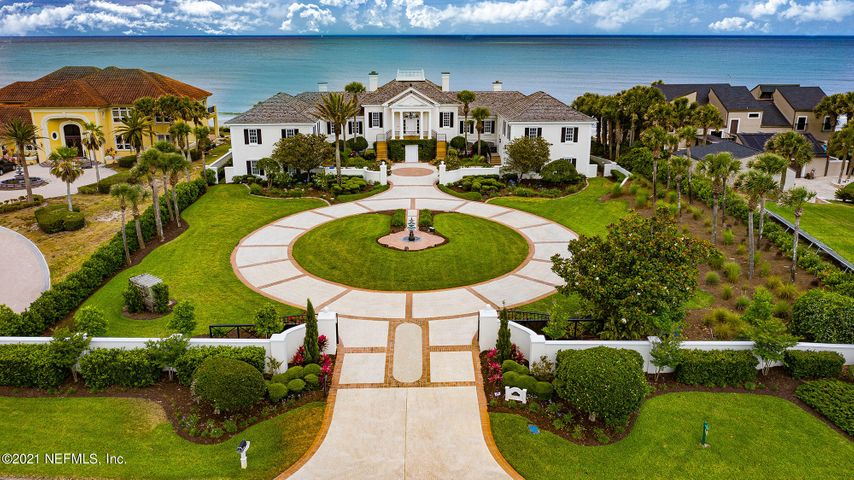 This Neoclassical oceanfront estate was redesigned in 2017.  An impressive presence reminiscent of the Golden Age of Hollywood.  Palatial living space describes the grand sweeping 2nd floor entrance to a  reception hall with hardwood floors, a large fireplace and floor to ceiling glass doors to a spacious oceanfront balcony and magnificient views.  Designed to entertain, the kitchen has backlit semi-precious imported stone from Italy, the finest in appliances with ocean views beyond the family room. An elegant Owner's suite features a new bath, oceanfront soaking tub, large walk-in shower and 16 x 12 dressing room with custom cabinetry. The newly designed first floor has many flex rooms with direct access to a covered lanai & infinity pool, built in 2018. This estate is stunning in stature