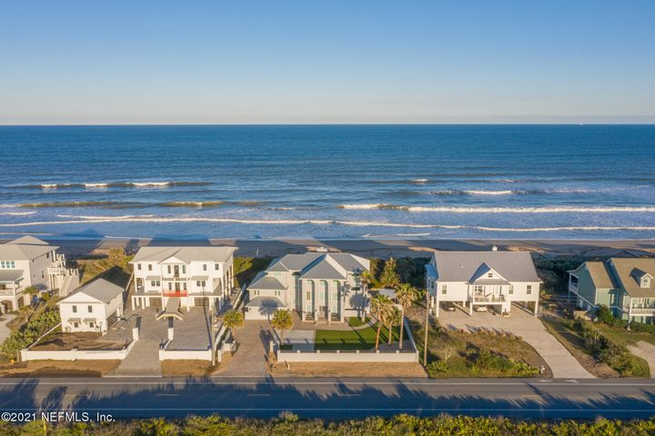 Live the dream every day from this beautiful Oceanfront Estate situated on one of the highest dunes in Ponte Vedra Beach. Upon entering the extended driveway through a double gate entry, you will be greeted immediately by the grandness of this home. Extensive and incredible views of Guana Reserve where you will enjoy never-ending Florida sunsets to the west, and the Atlantic Ocean accompanied with morning sunrises to the east. This property offers little to no lawn maintenance featuring an always green turf front lawn and river rocks spanning the side and backyard. This home features a guest suite or apartment that has been completely renovated. Private access separate from the main home, making it very secluded and accessible.  Complete with a spacious living room, large bedroom, bathroom, and a full kitchen. This 4 bedroom, 3 bath home has been lovingly kept by the second owner. Entering through the front door you will find yourself in a spacious entry way with a modern style floating staircase. High impact windows and doors throughout for protecting your Florida home. After ascending to the second floor you will find the grand family room with a stacked stone fireplace from floor to ceiling with a reclaimed wood mantle. The home is lit with an abundance of natural light from the large windows that hold expansive ocean views. To your left is the formal dining room, with an entrance leading to 2 of the bedrooms, bathroom, and laundry room. To your right is the kitchen complete with granite countertops, an abundance of cabinetry and an eat in breakfast nook. The doors open for direct access to the deck offering a great space for indoor, outdoor entertaining. Sit out on the deck and feel the sunshine and the salt breeze all around you. The deck leads out to the boardwalk that provides private beach access and hosts an additional seating area. The beach oftens feels like a private beach being that the nearest public access is 1.5 miles away. Retreat upstairs where you