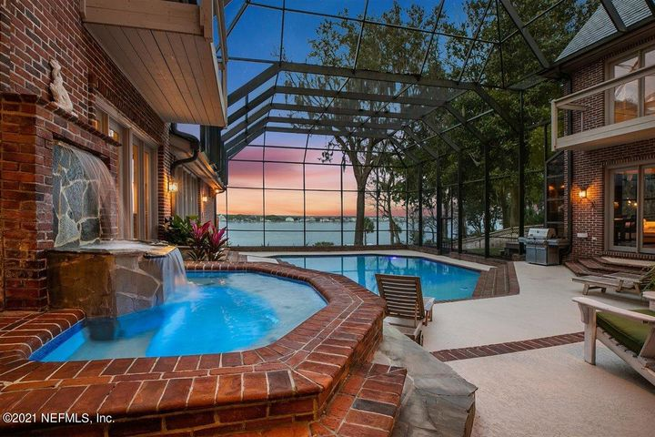 DON'T MISS THE VIDEO. Breathtaking riverfront estate surrounded by the historic Timucuan Nature Preserve, Fort Caroline National Park, Spanish Pond nature trails, and on historic St. Johns Bluff overlooking the St. Johns River, this is truly a one of kind property. Jacksonville's up-and-coming luxury riverfront community located midway between the city and the beach, has quick access to the ocean to your favorite fishing spot. Launching your boat from a 2,500 SF dock complete with floating dock, covered boat slip with a 12,000 LB boat lift. Water depth is +/-16' deep water so tides are no issues.   Directly on the dock platform is a full 1,600 SF dock / guest house, providing limitless options for recreation and entertainment on the water. READ MORE. Enter the gated video-monitored estate and you feel the true feeling of privacy, security, and unparalleled serenity. As you drive up the 400' driveway, you will immediately notice the details of this custom home: natural slate roof, brick exterior, large parking courtyard, stunning leaded glass front doors. Beyond the glass doors are a large marble foyer with an impressive fully open grand staircase leading to the second floor gallery. The living / great room and dining room have 26' soaring beamed and vaulted ceilings. Behind the staircase is an intimate bar overlooking the pool and river. The great room's massive wood burning fireplace is flanked by library styled bookcases. Large mezzanine creates an area for party guests to mingle and enjoy the river views. Intimate river view bar adds to ambience. Vast succession of windows surrounding the mezzanine delivers stunning views of the St. Johns River while filling the house with light as you gaze over the enclosed pool and spa on to the river.    Most of the living areas have a river view accomplished by balconies and French doors surrounding the pool area. Enjoy the ever-changing view of the river from morning coffees to nighttime cocktails as the sun goes down. A ser
