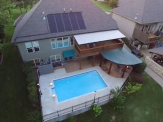 Drone photo of lakeside with pool, outdoor kitchen and fire pit