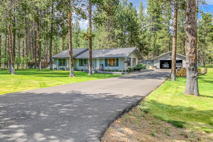 Beautifully manicured lawn and fenced yard surrounds this oasis