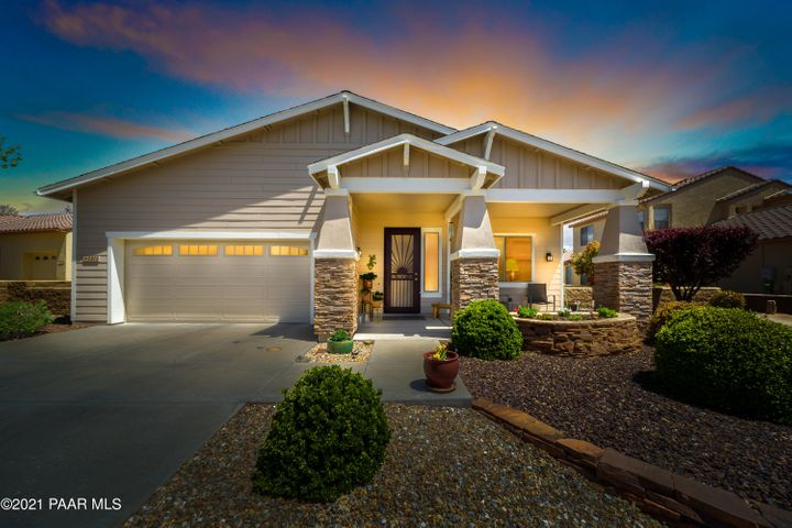 Front Exterior with Custom Security Screen Door, 26 Owned Solar Panels, Covered Front Porch & Stacked Stone Accents.