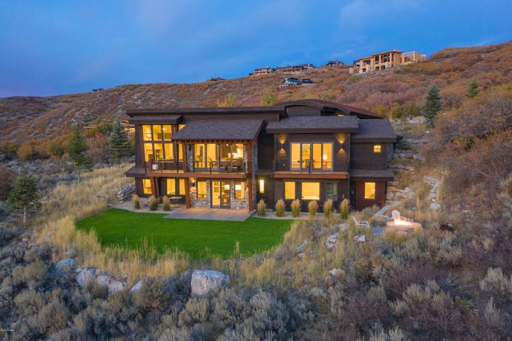 The large windows of this carefully designed, modern home perfectly frame the stunning views of the canyons and cliffs welcoming wildlife on your own 2.5 acres which is one of the larger lots in Promontory. The windows throughout the home capture the panoramic views from every room, and you'll frequently see deer and elk on the game trails that run through the property (sometimes over 100 deer or elk). The home features main floor living with the kitchen, great room, dining and master all on the first floor with a nicely planned floor plan and flow. The kitchen is nicely designed with an oversized quartz island, hidden pantry and stainless appliances - perfect for any chef. Downstairs also opens to the views with large windows from the family room and additional bedrooms each with private bathrooms - plus you'll find a nice area for wine storage. Upstairs is a private mother-in-law suite that is ideal for family or an additional bedroom for a nanny or caretaker. And probably one of the best qualities of this home is the over-sized, heated garage that easily fits any three cars plus all your mountain toys.