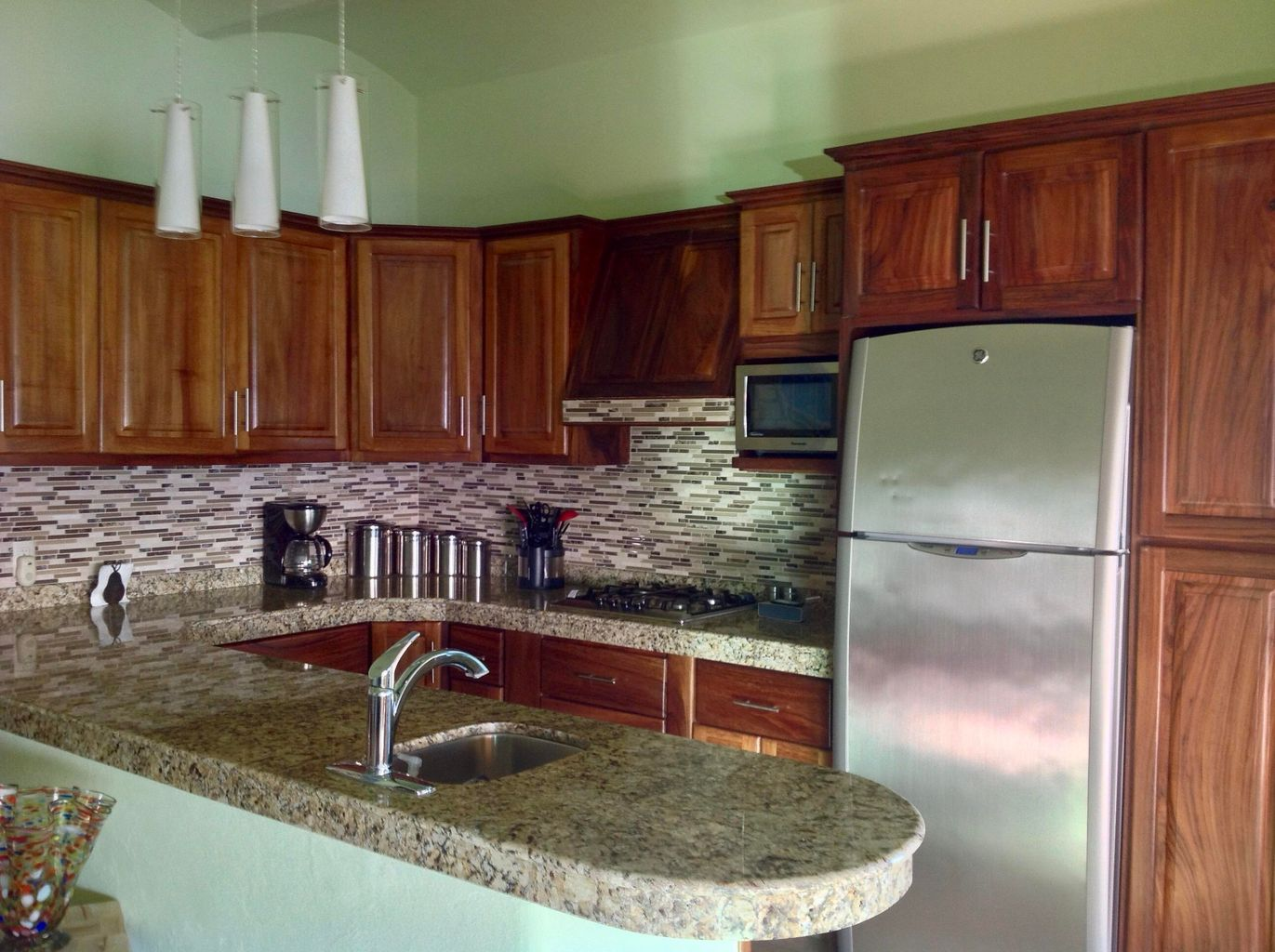 Modern kitchen includes granite counter tops, stainless steel appliances, beautiful parota cabinetry with lots of storage