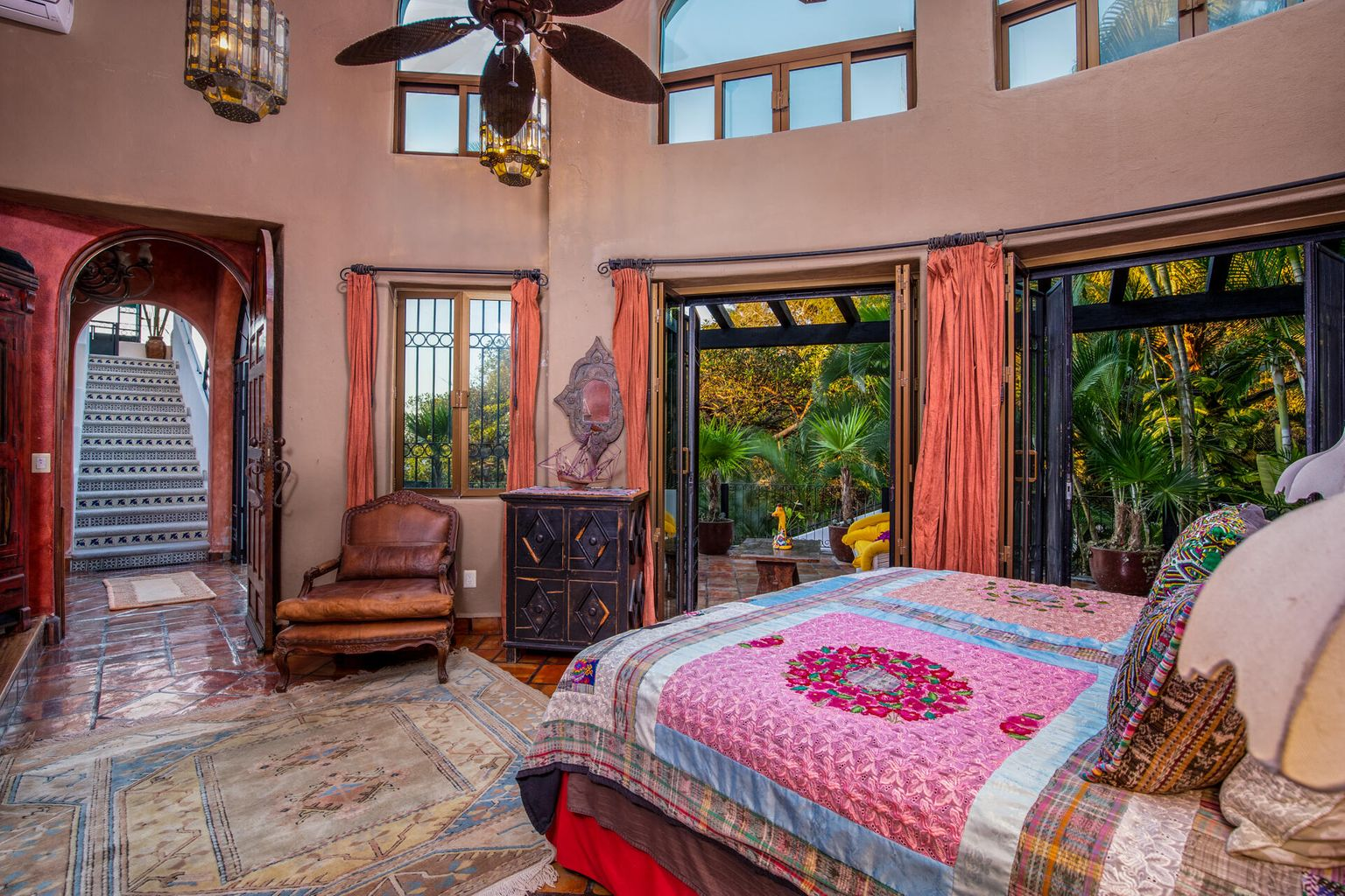 French doors open to the terrace with views of the garden/jungle