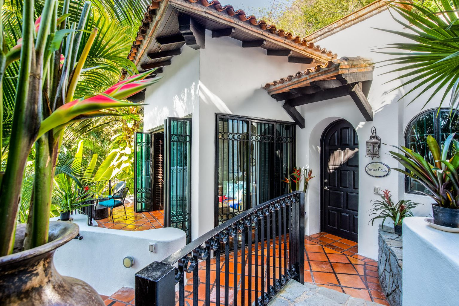 Large iron doors and plantation shutters open from the front and sides