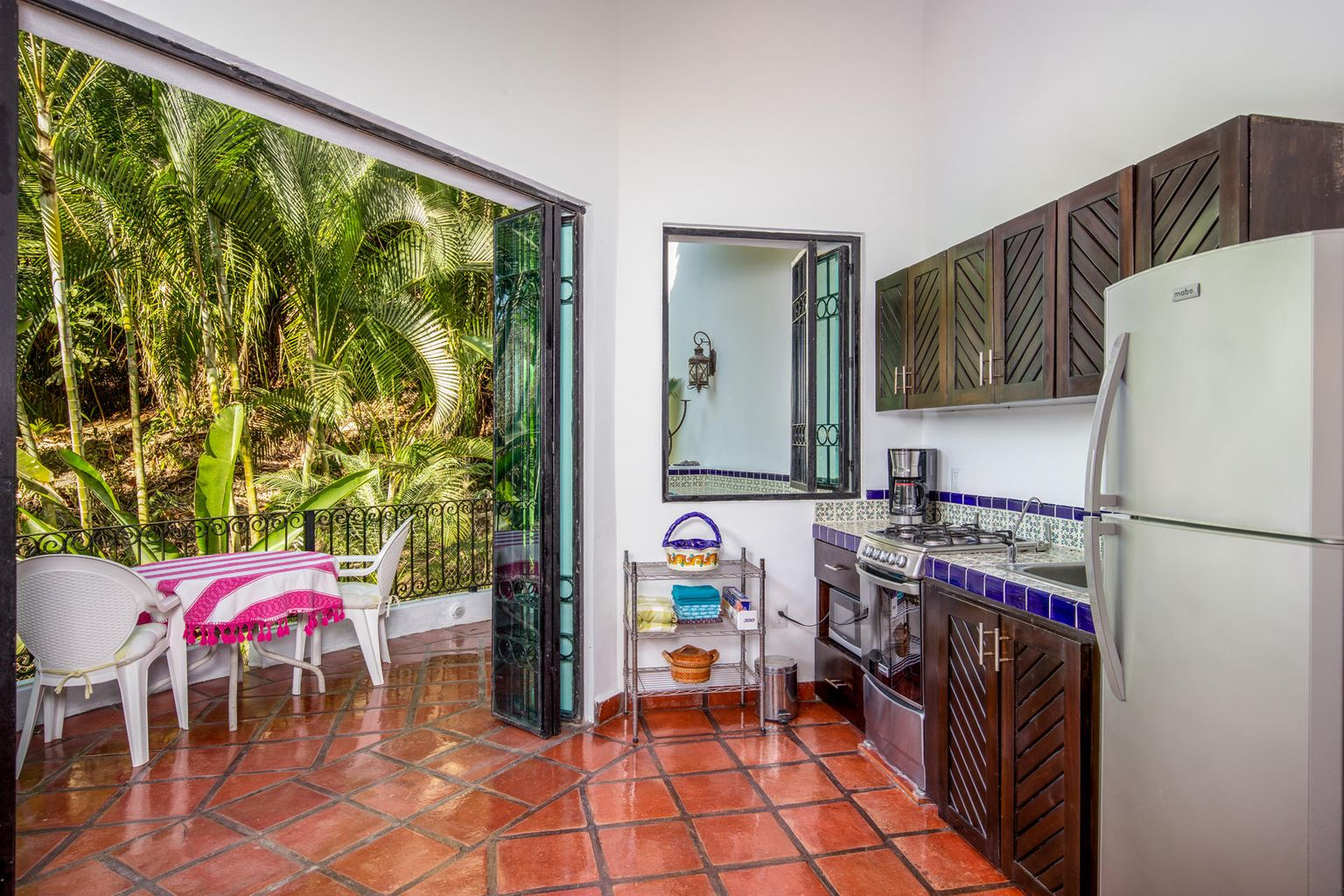French iron doors open to the jungle and arroyo below