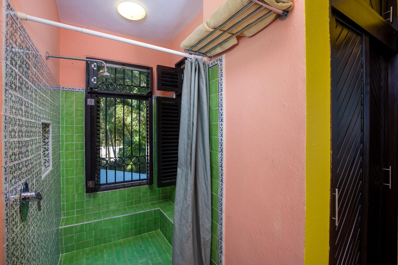 Large walk-in shower with iron windows on both sides with jungle view