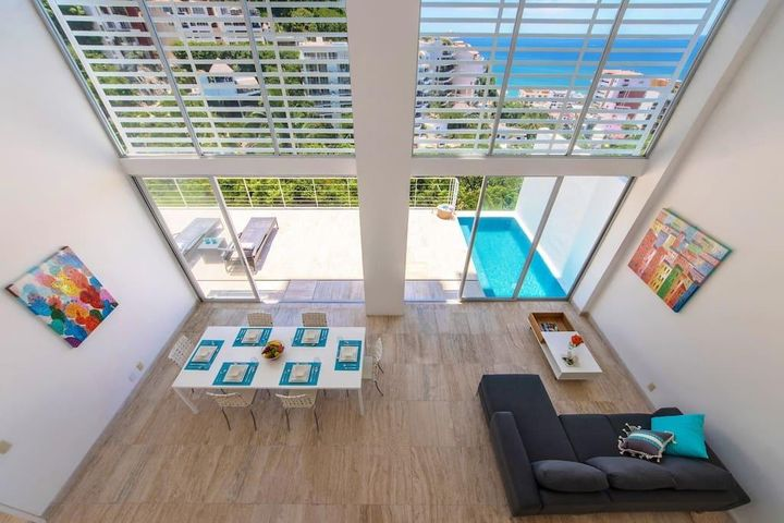 Main floor living Room with views. Double height living space and private pool.