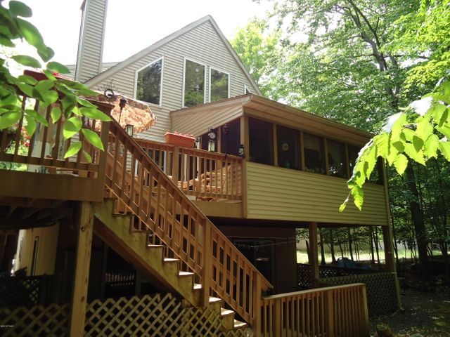 Exterior of home with wrap-around trek decking facing green area.