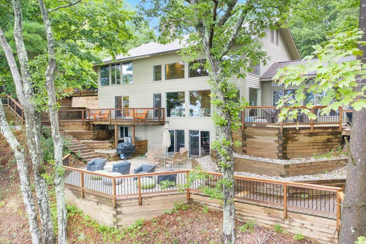Your own private private Lake Michigan summer retreat or year-round home awaits you. Situated on 3.3 acres with over 200 feet of Lake Michigan frontage with an easy egress to the ample shoreline this contemporary home will meet all of your expectations. The current driveway comes through Meinert Park beach parking area; the home also offers a shared easement to Flower Creek Road for an alternative route. Flower Creek Dunes Preserve will be your neighbor to the north a more than 35 acre property with winding trails and unspoiled nature areas. The main floor of this home offers two large bedrooms, a full bath, laundry, kitchen, dining or sunroom, soaring ceilings in the living room complete with one of three fireplaces and an architectural curved staircase. Upstairs you will find a loft area, a bonus room currently used to sleep six and a gorgeous master suite complete with fireplace, soaking tub, floating bed and access to the cascading deck spaces. In the lower level you will find a full second kitchen, recreation room with fireplace, second eating area and a full additional bedroom with private bath including a jetted tub. Outside there are decks on all three levels to enjoy the warm summer evenings of crisp fall fireside chats. The property has been used a successful rental and summer retreat. Truly one of the most private and beautiful retreats along the shoreline.