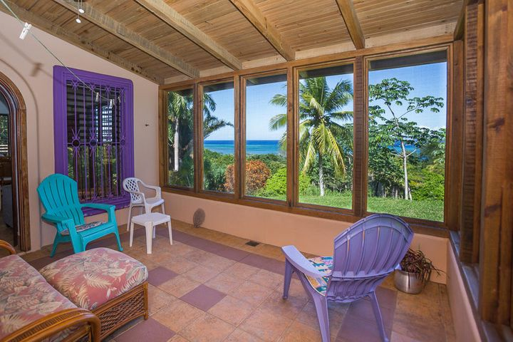 Spacious screened in porch on the main floor offers ocean views and lush tropical garden view