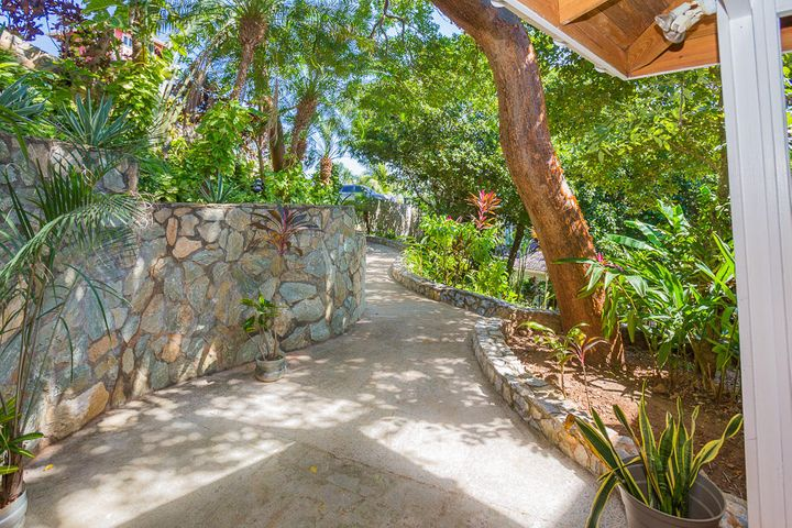 Enjoy the tropical landscaping that surrounds the house and offers the walk way from the parking area to the home