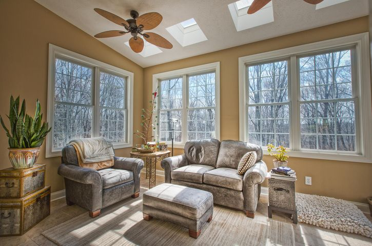 Sun room is located just off kitchen and opens onto the deck