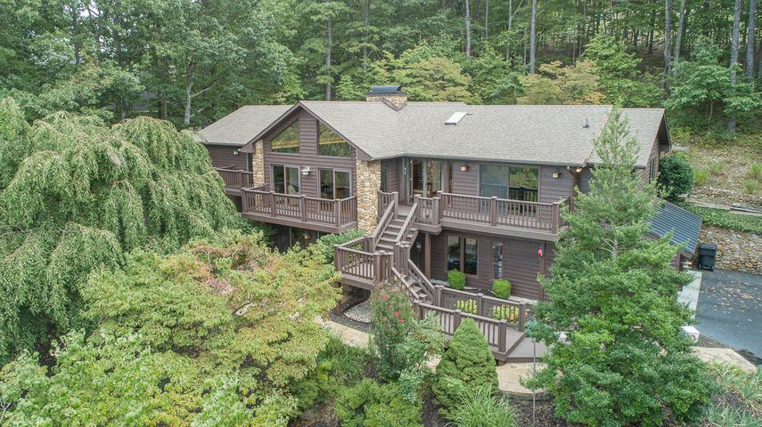 Perfectly perched on a wooded, landscaped lot in Hunting Hills