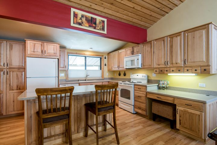 Newly remodeled with solid surface counters, hickory cabinets, pullout drawers in island and desk area.