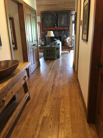 Hallway looking from entry to living room. New h/w flooring, custom paneling and new doors.