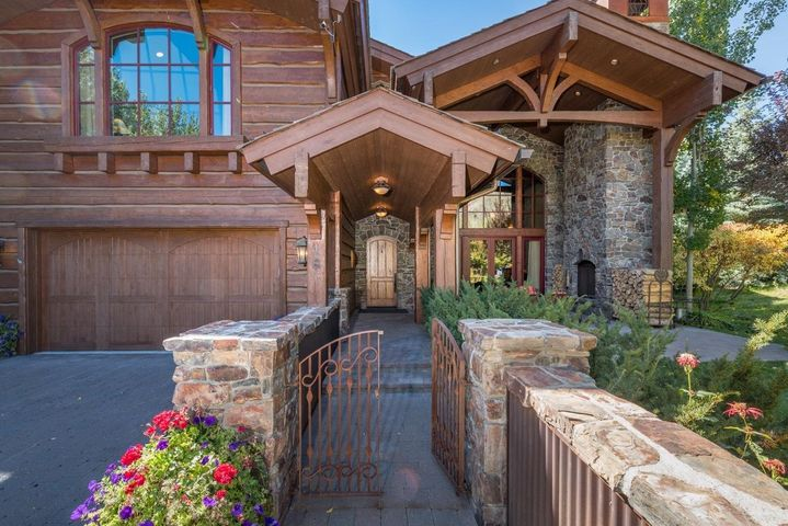 Grand entrance with custom iron gate, stone wall and