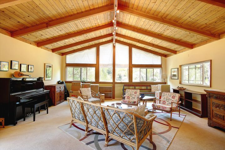 Huge family room with vaulted ceilings, lots of light and large windows that look out to lush trees.