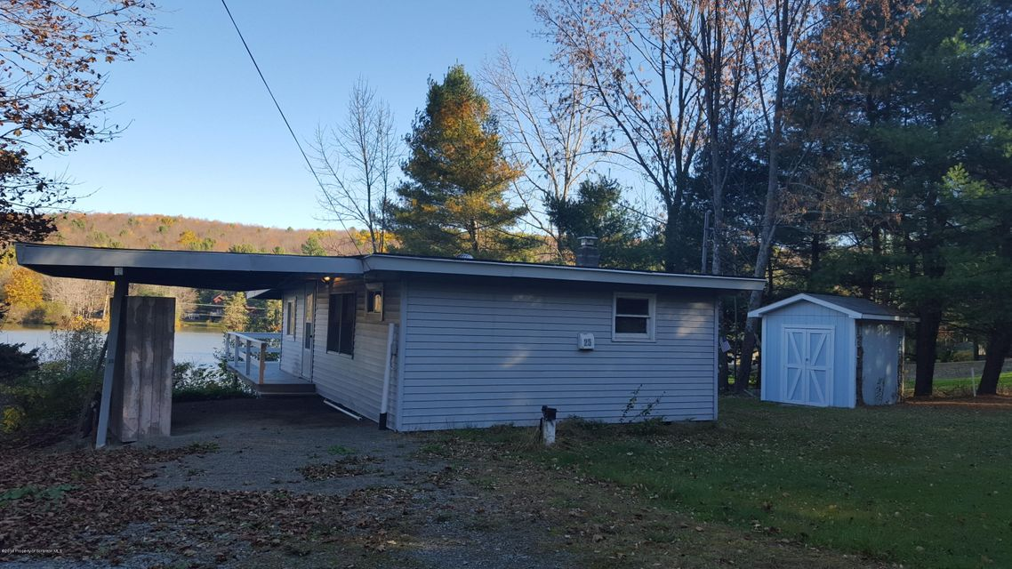 Quaint cottage on Bel Aire Lake. Large lakefront with room to expand home. Features include open plan, bedroom with lake view, wrap around deck, carport, shed, babbling stream and additional land across private road.
