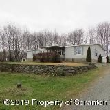 Double wide w/ additions and 1 single wide mobile home w/ additions go with this property. Live in one and rent the other.  There are 2 garages here as well. Gas rights transfer.